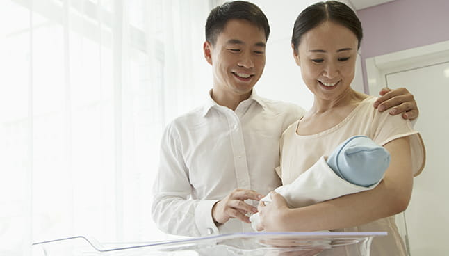 Asian couple holding an infant