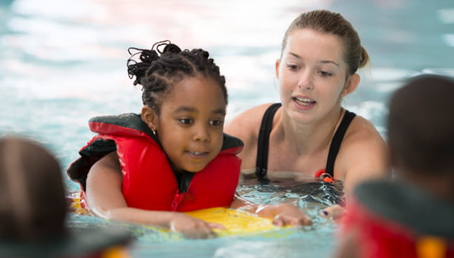 Girl with life jacket getting a swim lesson