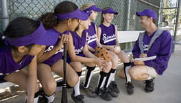 Coach talking to girls softball team on the bench